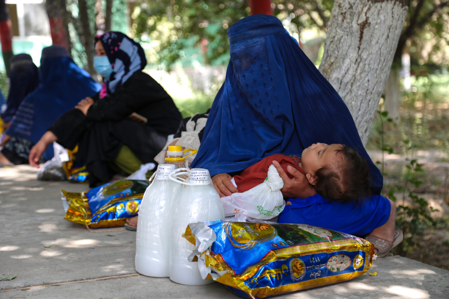 Afghan mother and child receiving emergency relief from STEP