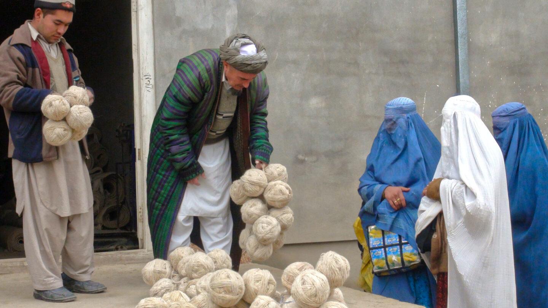 Afghan weavers collect yarn at the bazaar